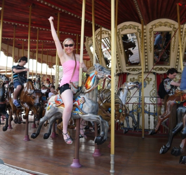 girl riding carousel attraction theme park
